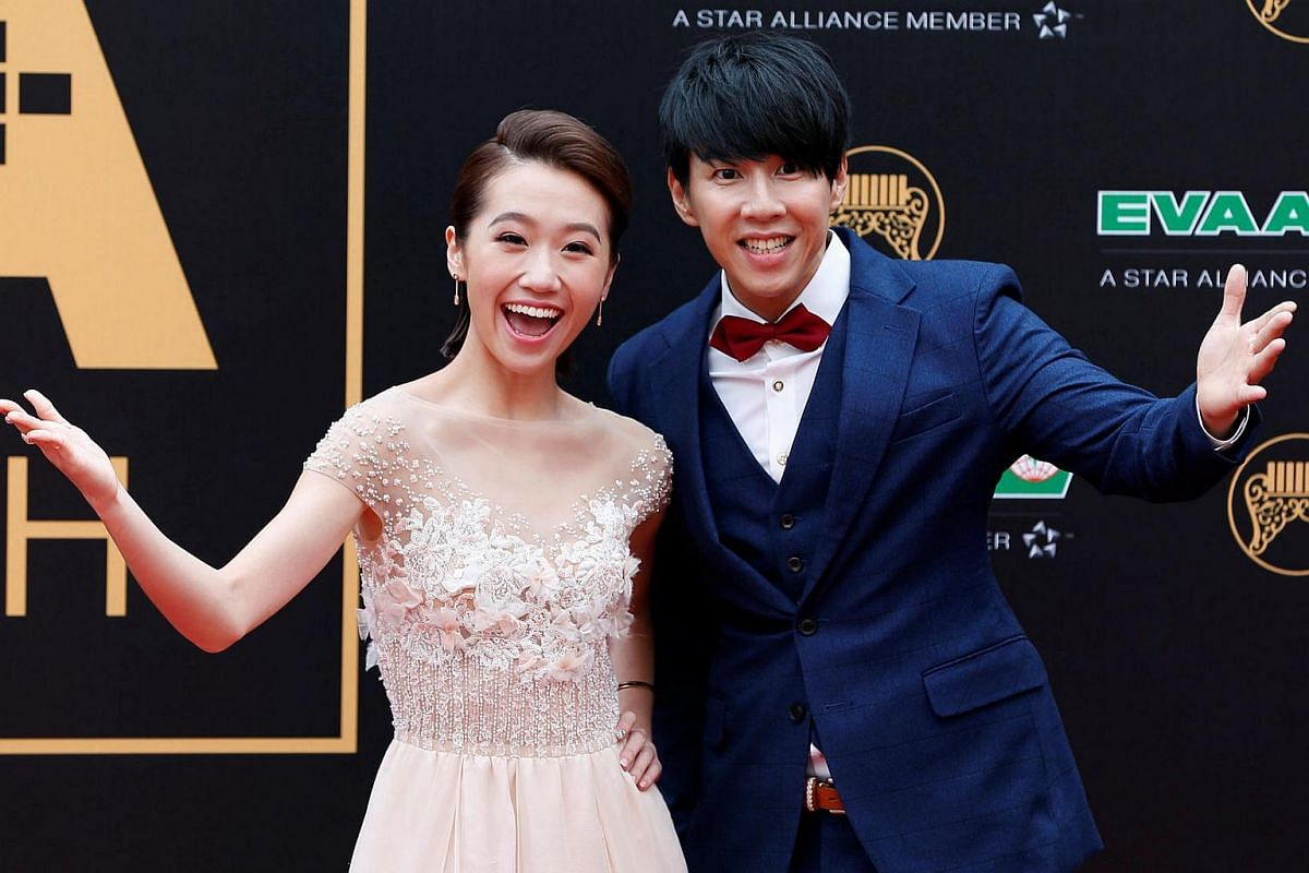 Actor Dennis Au poses with host Huang Lu Tz Yin on the red carpet.