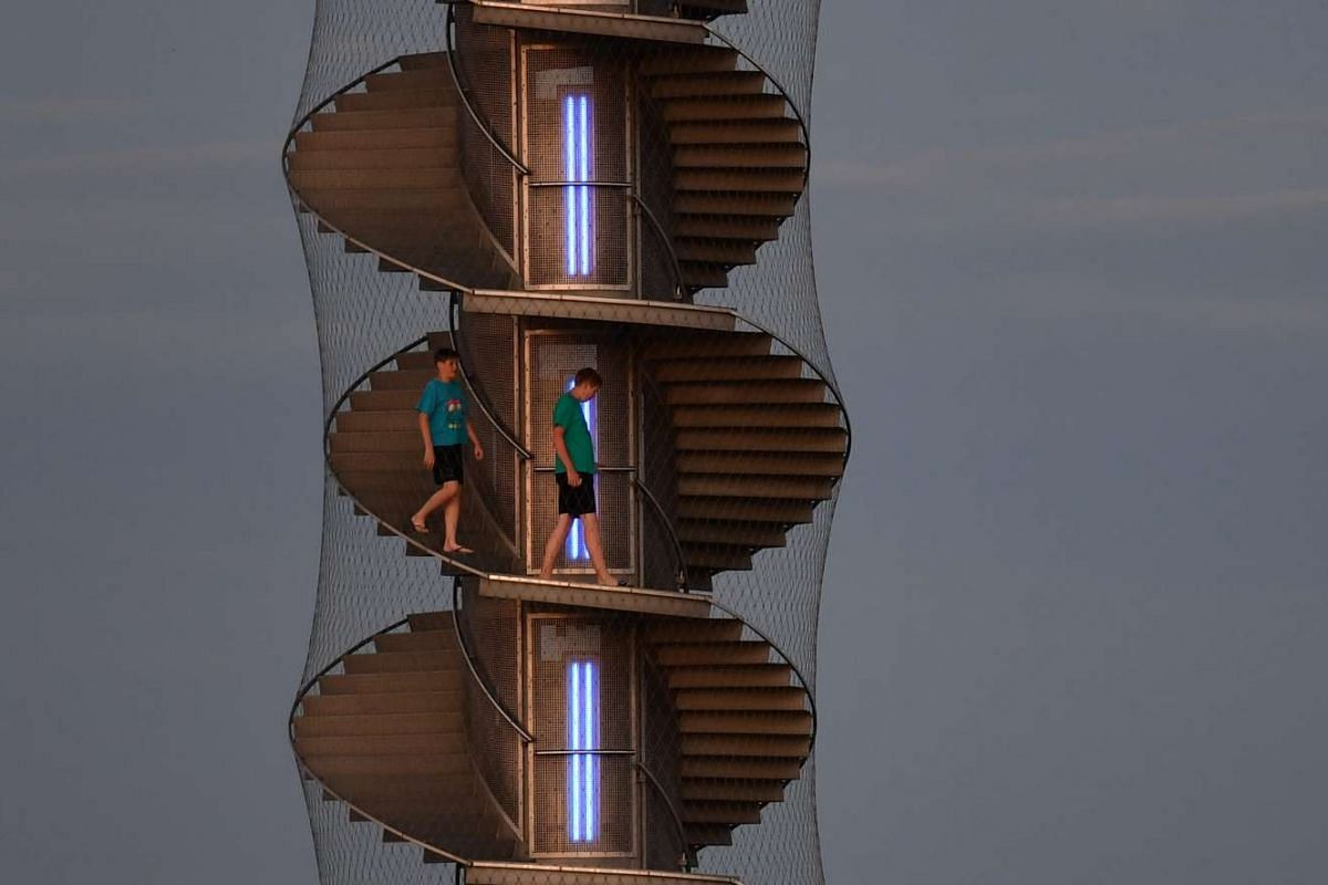 Tourists stepping down from the Pegelturm Goitzschesee tower in the night light near Bitterfeld, Germany, on June 26, 2016.