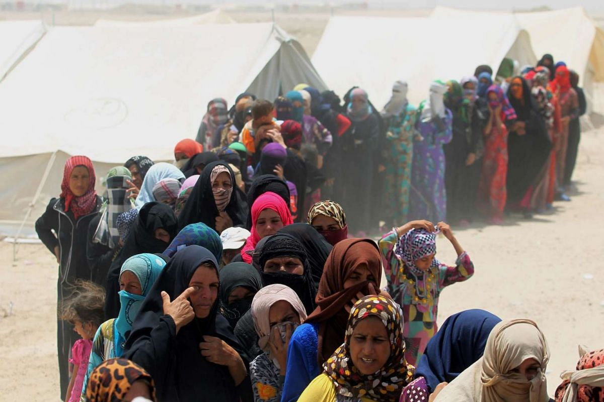 Iraqi women displaced from the city of Fallujah queue up to collect aid distributed by the Norwegian Refugee Council at a newly opened camp where they are taking shelter in Amriyat al-Fallujah, on June 27, 2016.