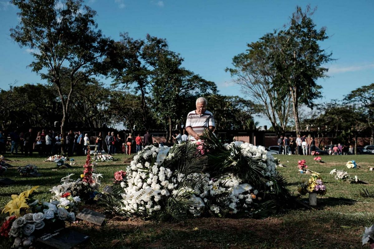 A man holds a prayer after the funeral of Gisele Palhares Gouvea, in Rio de Janeiro, Brazil, on June 27, 2016.