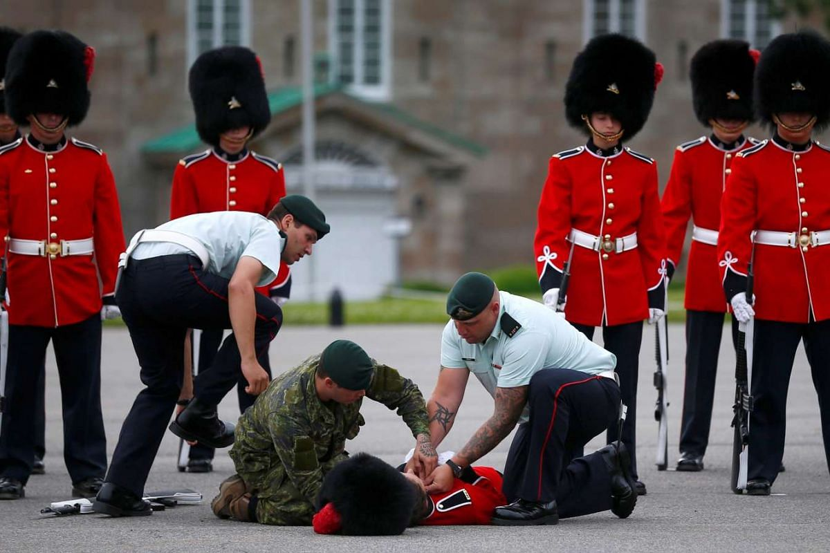 A member of the guard of honour is attended to by colleagues after fainting prior to Mexico's President Enrique Pena Nieto's inspection at the Citadelle in Quebec City, Canada, on June 27, 2016.