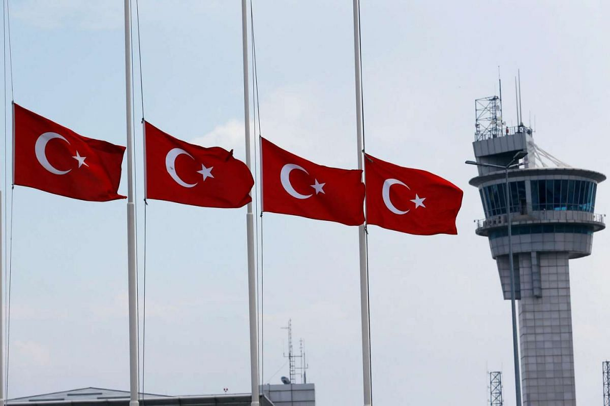 Turkish flags, with the control tower in the background, fly at half mast at the country's largest airport, Ataturk international airport in Istanbul on June 29, 2016, following Tuesday's attack.