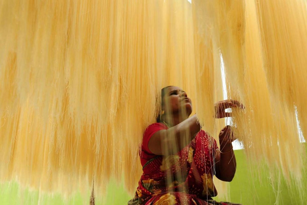 "An Indian woman sorts strands of drying seviiyan - thin vermicelli - which is used for the preparation of ""sheerkhorma"", a traditional sweet dish prepared by muslims during the holy month of Ramadan, at a food factory in Chennai on June 28, 2016."