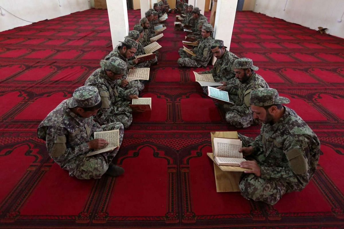 Afghan National Army soldiers breaking the fast during the holy fasting month of Ramadan at their military base on the outskirts of Herat, Afghanistan on June 28, 2016.