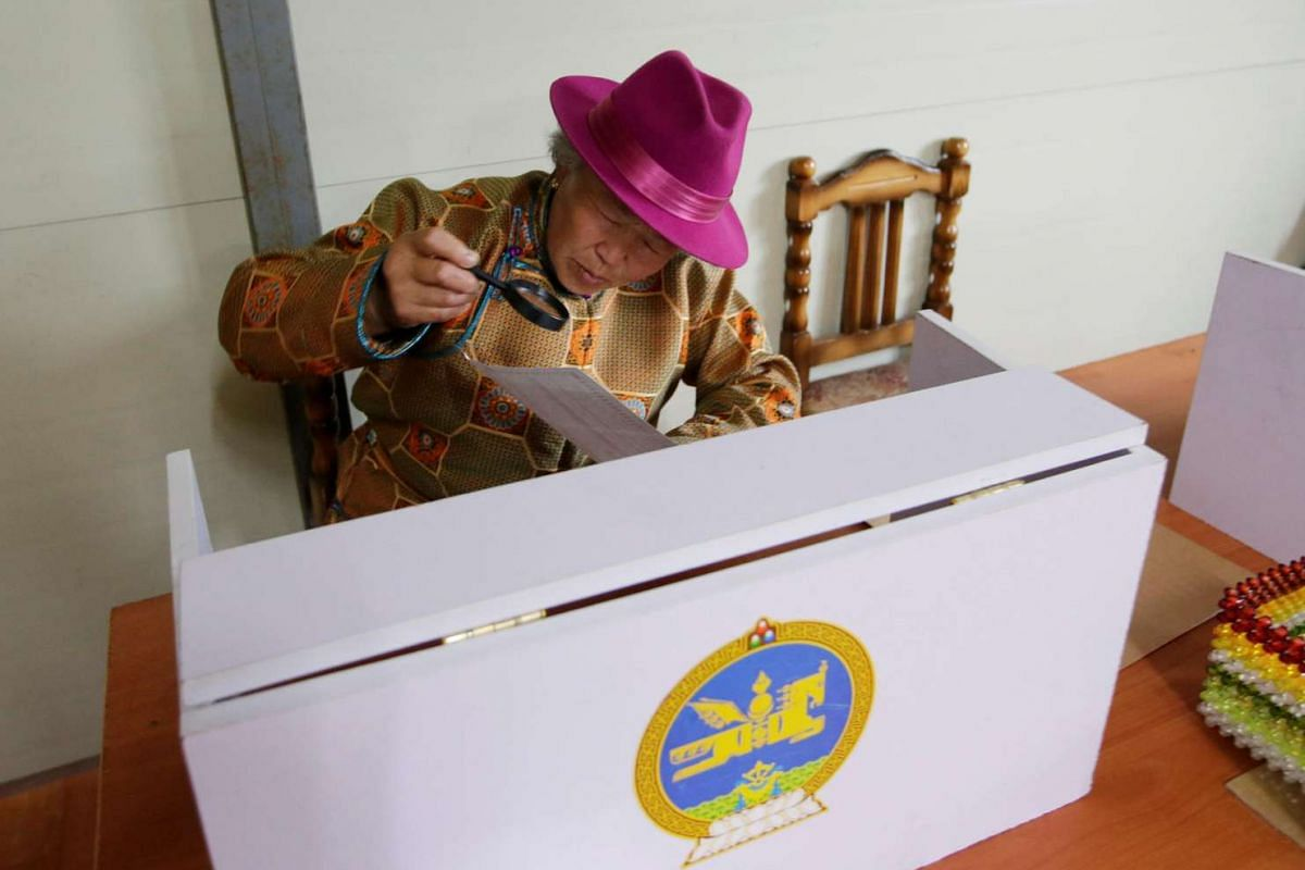 A villager reads her ballot paper before she fills it for the parliamentary elections at a polling station on the outskirt of Ulaanbaatar, Mongolia on June 29, 2016.