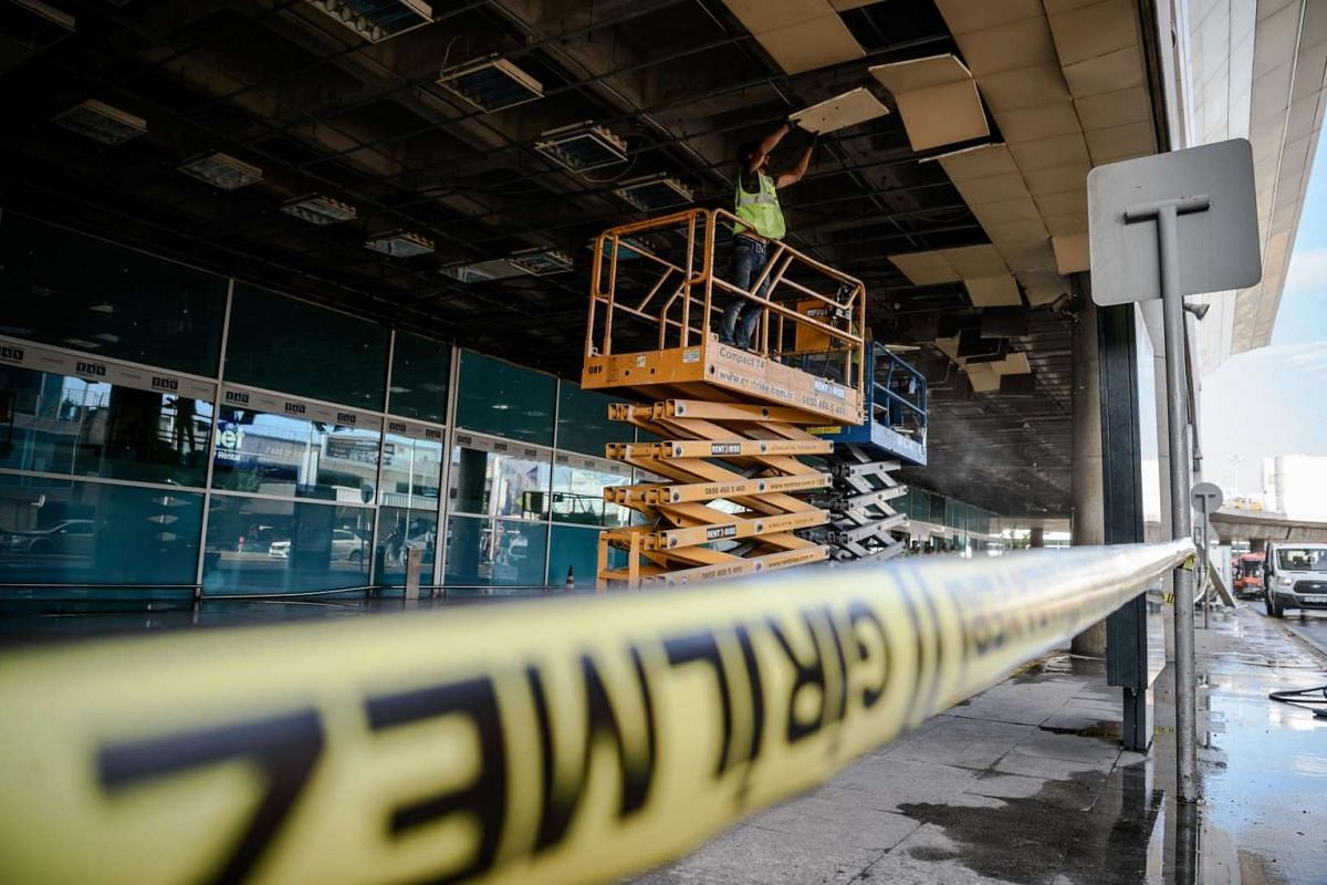 An employee works in the cordoned off area on June 29, 2016, a day after blasts rocked Ataturk international airport in Istanbul, Turkey.