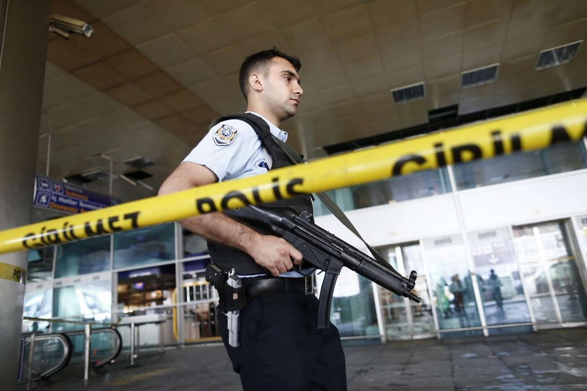An armed Turkish policeman patrols behind a police line at Ataturk international airport in Istanbul, Turkey on June 29, 2016.