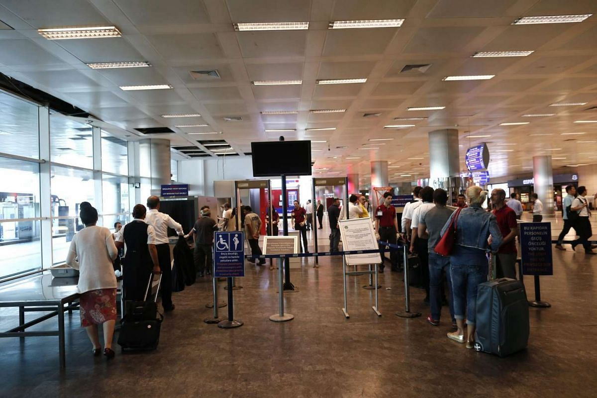 Passengers wait in a line for security check at Ataturk international airport in Istanbul, Turkey on June 29, 2016.