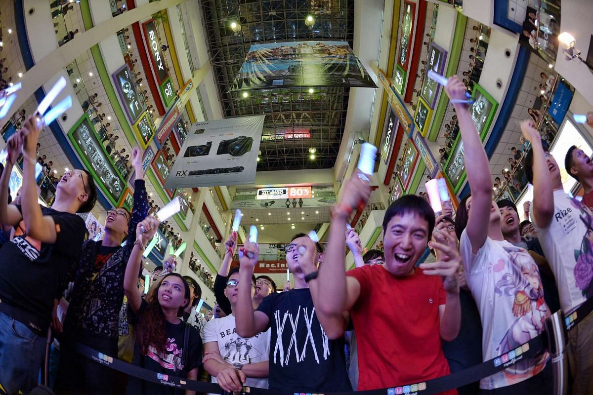 Anisong fans singing and waving LED lights in unison inside the atrium of the Funan DigitaLife mall on June 12, 2016, during the Funan Anime Matsuri 2016.