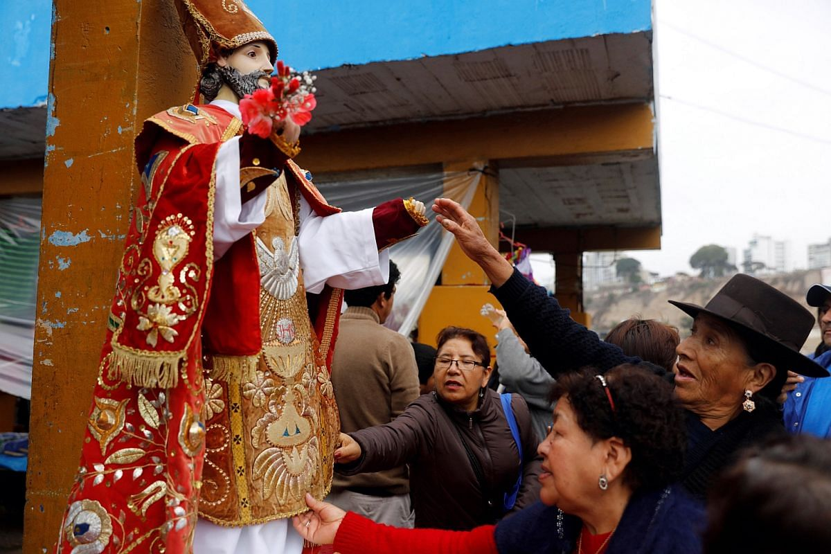 Peruvians commemorate the Day of the Fisherman by taking a statue of Saint Peter out on a boat along the coast in Lima on June 29, 2016.