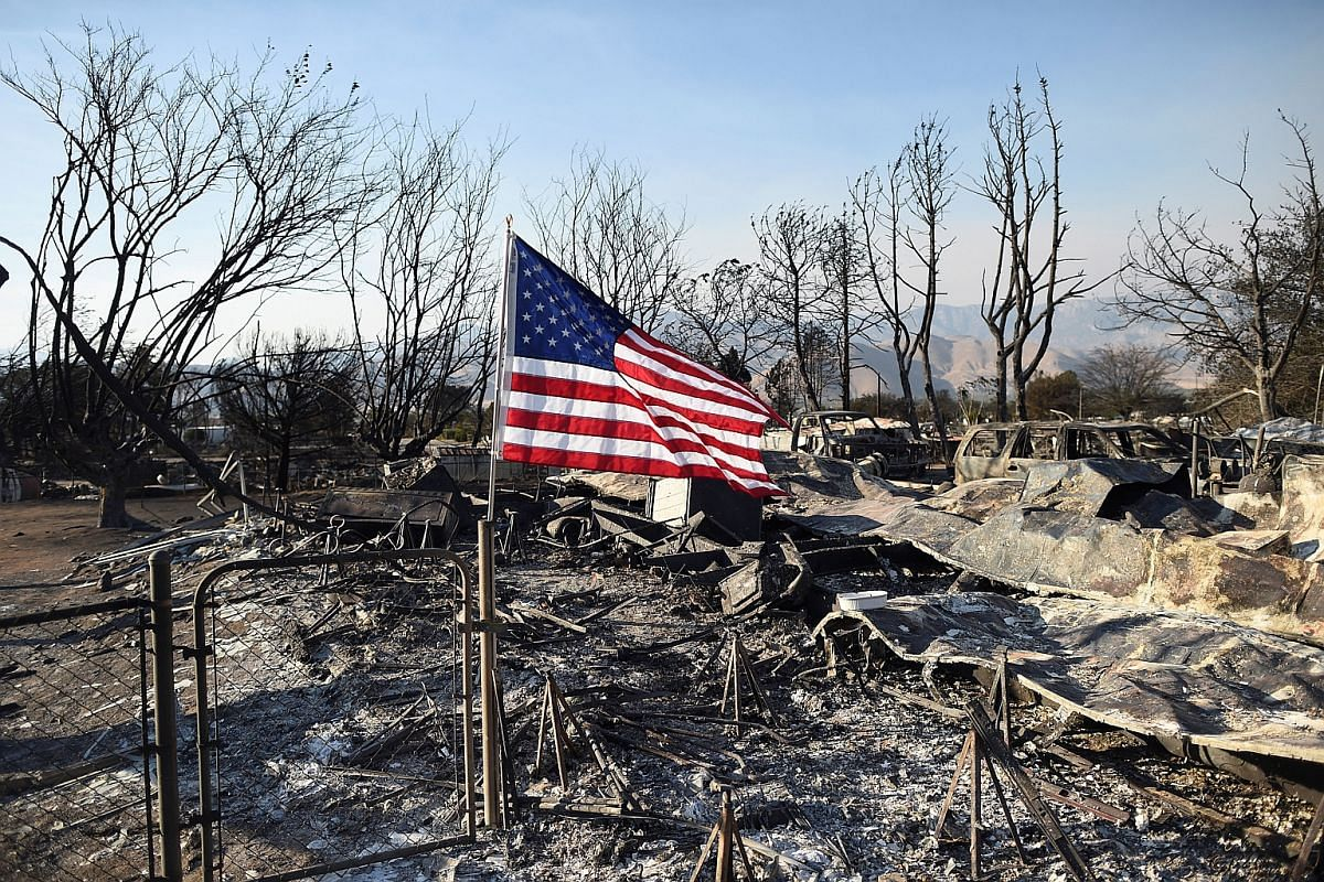An American flag flies above wreckage at a residence leveled by the Erskine Fire in South Lake, California, US on June 26, 2016.