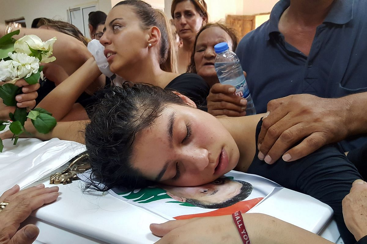 The daughter of Joseph Laous, who died after a suicide bomb attack in his village, mourns on his coffin during his funeral in Qaa, Lebanon, on June 29, 2016.