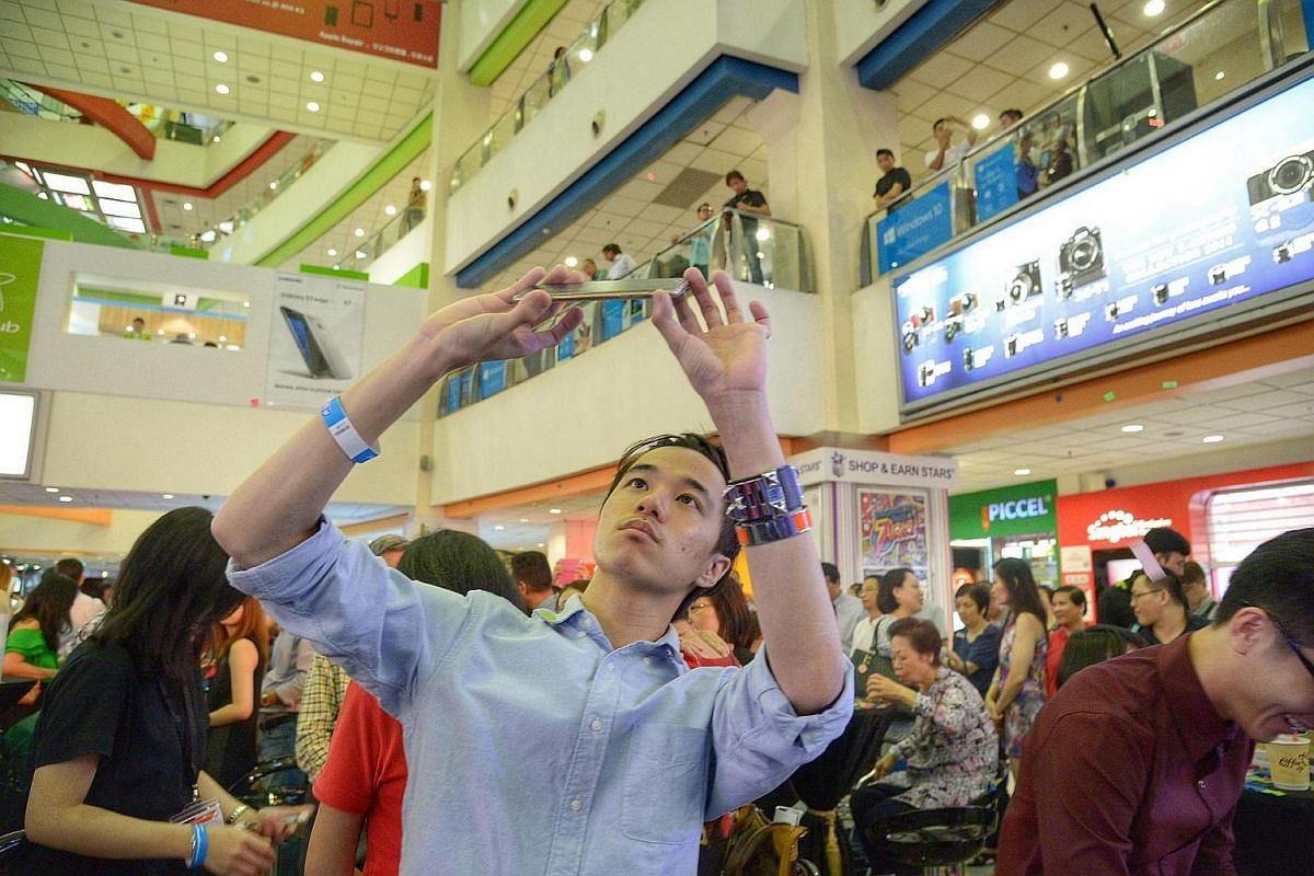 Mr Davious Chua, 23, a student from Republic Polytechnic, snaps a photo of the mall.