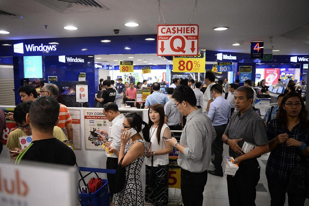 Customers queue up to pay for their purchases at Challenger on June 30.