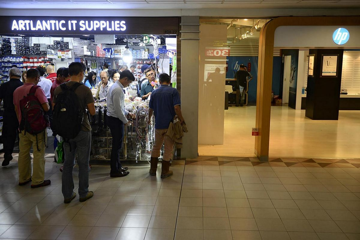 Customers patronise a shop bustling with business beside a shop which has been completely cleared out on June 30.