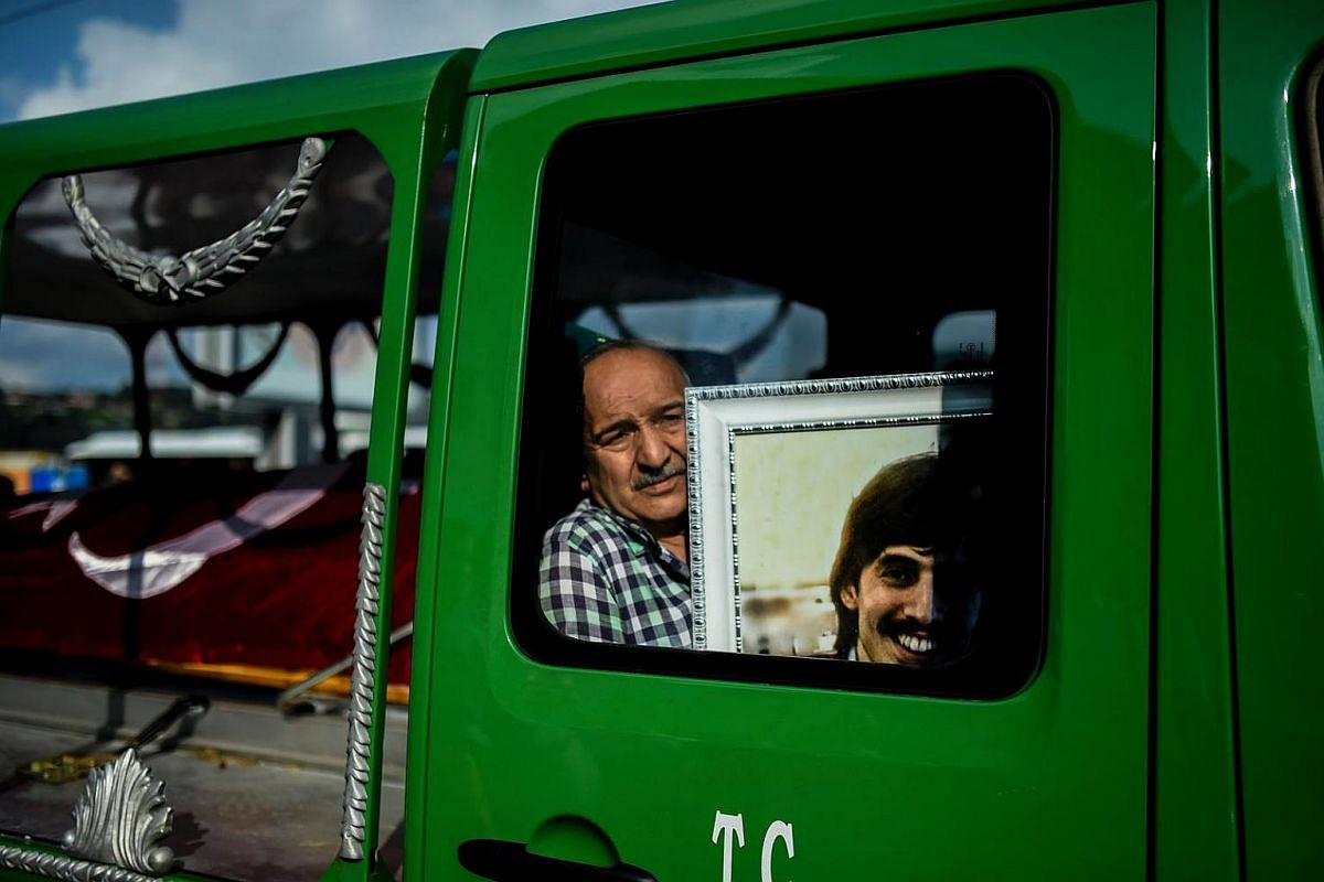 The uncle of Turkish teacher Huseyin Tunc, who was killed in the suicide attack, cries as he sits in the truck carrying the coffin during the funeral in Istanbul, on June 30.