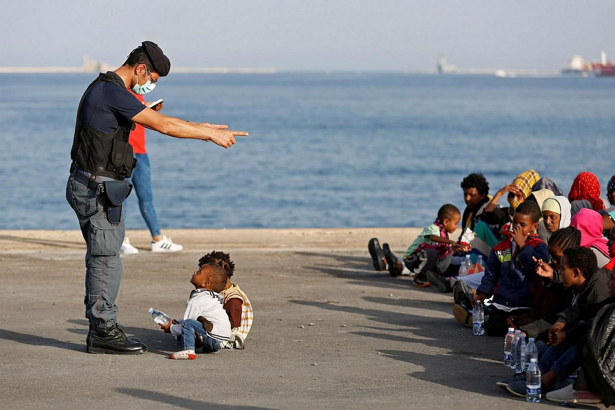A policeman talks with children as migrants disembark from Migrant Offshore Aid Station ship Topaz Responder in the Sicilian harbour of Augusta, Italy, on June 30.