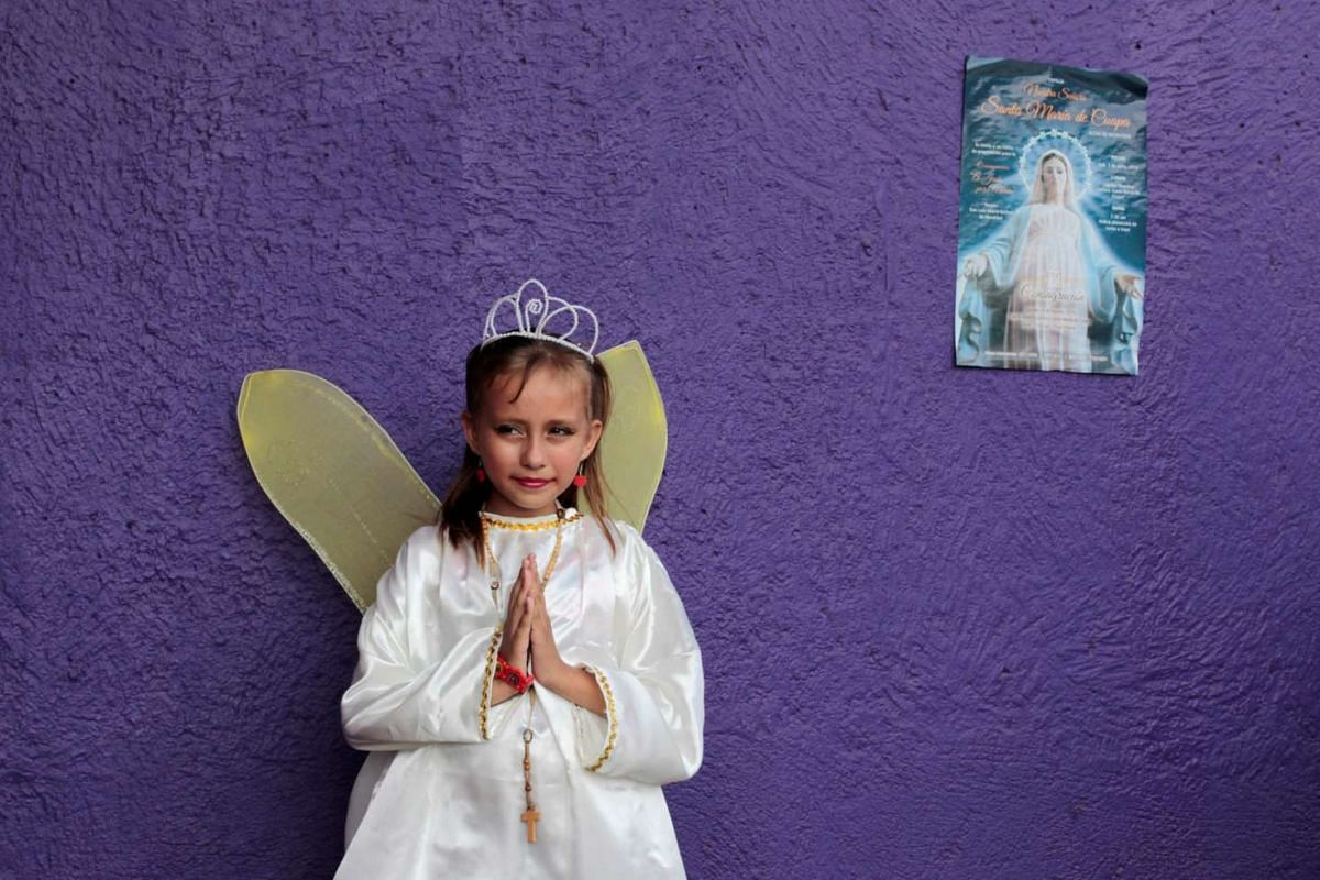 """A girl dressed as an angel takes part in a procession of """"Sangre de Cristo"""" at the Metropolitan Cathedral in Managua, Nicaragua on July 3, 2016."""
