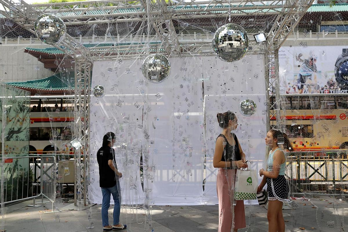 Visitors penning their wishes on the art installation Reaching for the Stars.