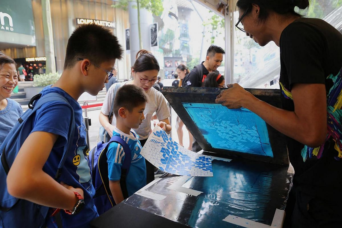 Volunteer Chris Chai shows (from left) brothers Barri Peh  and Baron Peh and their mother Cecilia Koh the image from the silkscreen printing.