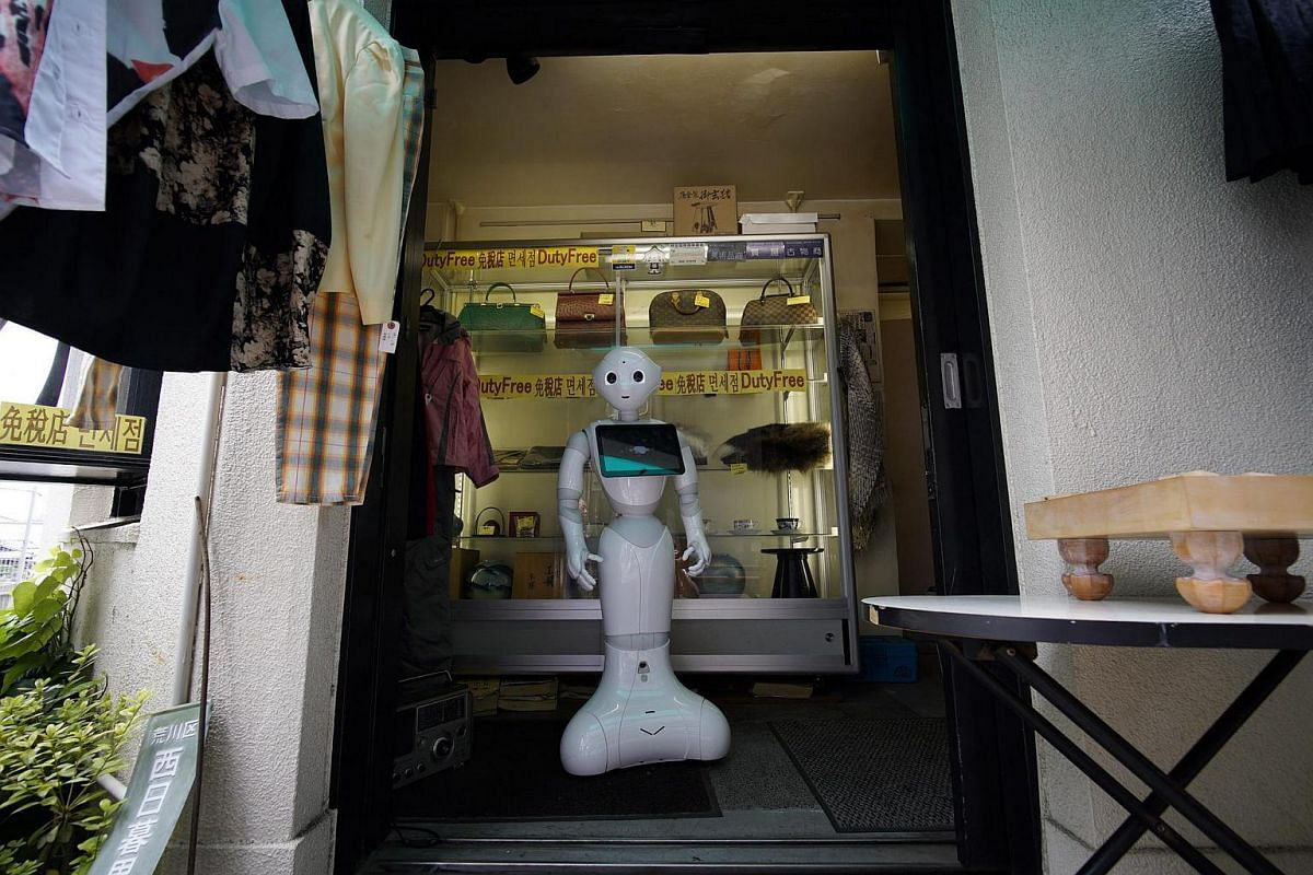 Humanoid robot Pepper stands at the entrance of the pawnshop of Tomomi Ota's father to welcome customers.