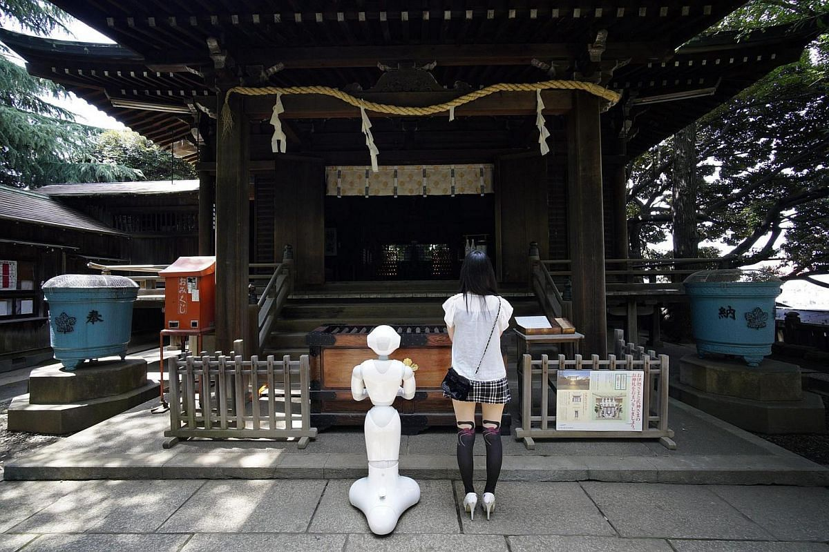 Tomomi Ota offers prayers at a local shrine with her humanoid robot Pepper.