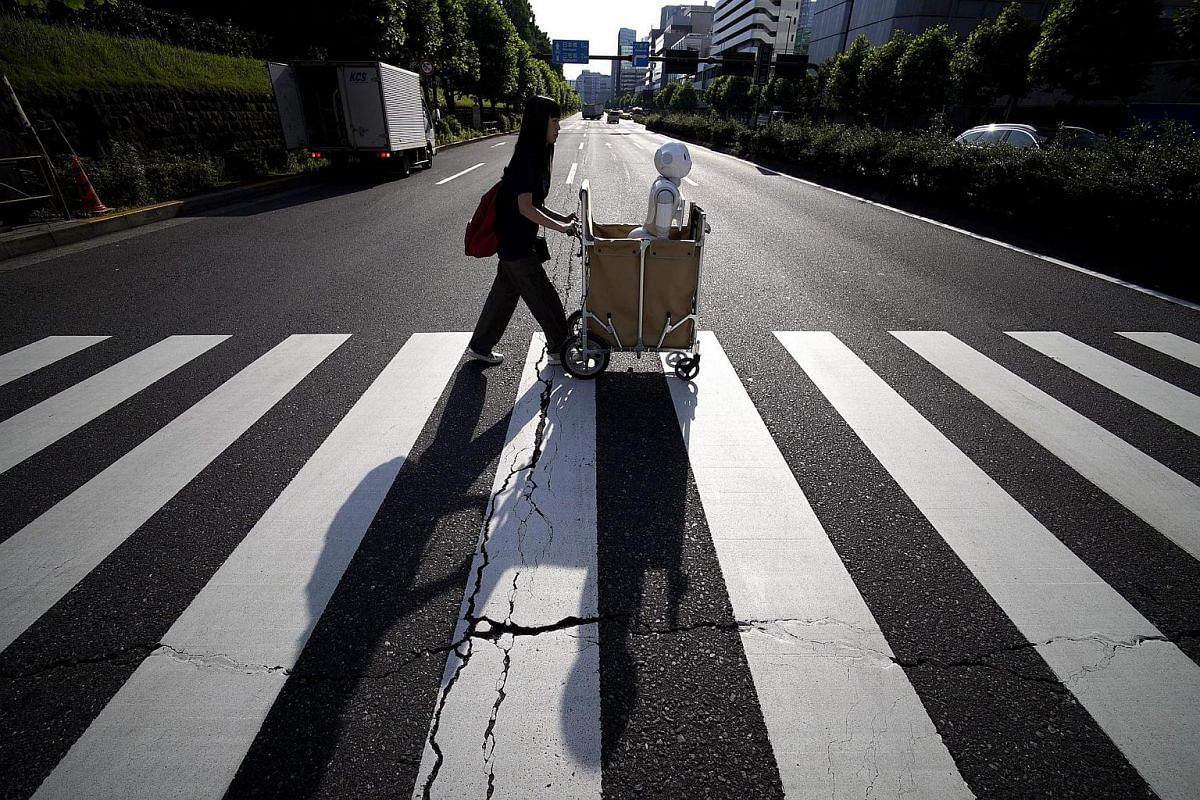 Tomomi Ota pushes a cart loaded with her humanoid robot Pepper on her way to work.