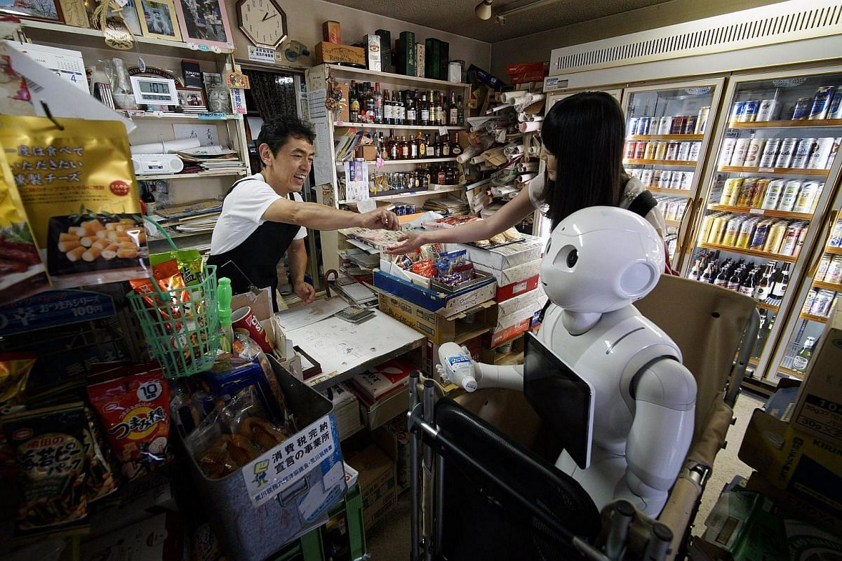 Tomomi Ota (right) buys a soft drink with her humanoid robot Pepper at a local shop.