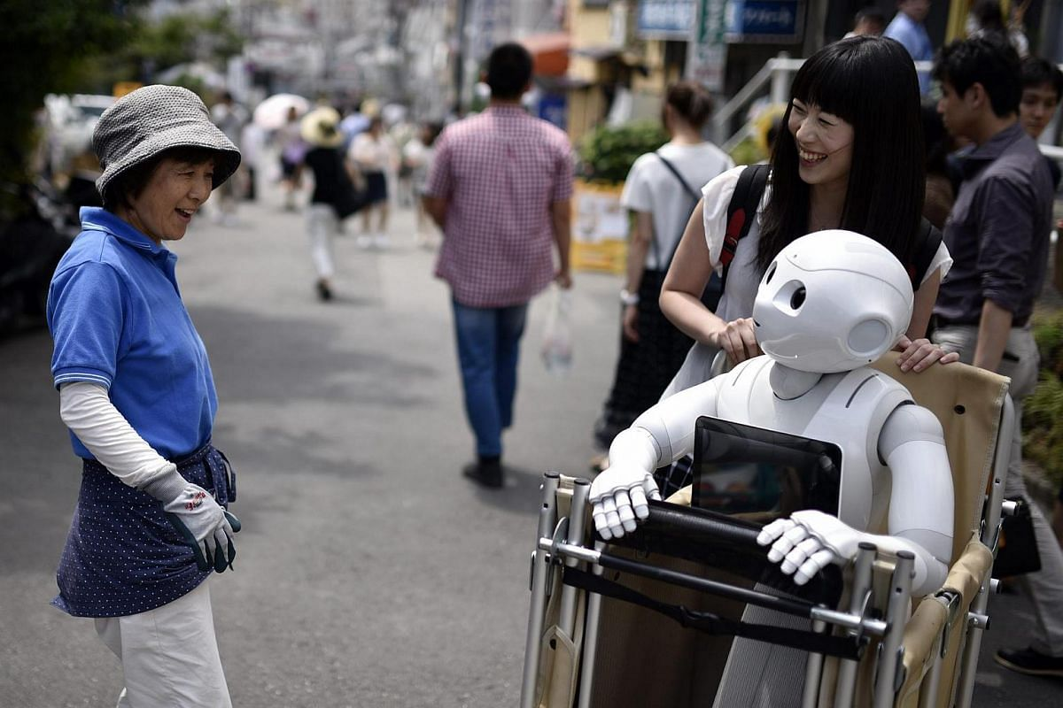A woman reacts as she sees Tomomi Ota (right) pushing a cart loaded with her humanoid robot Pepper.