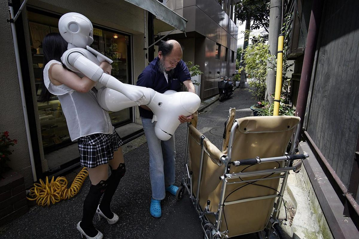 Tomomi Ota (left) and her father Norio load humanoid robot Pepper into a cart.