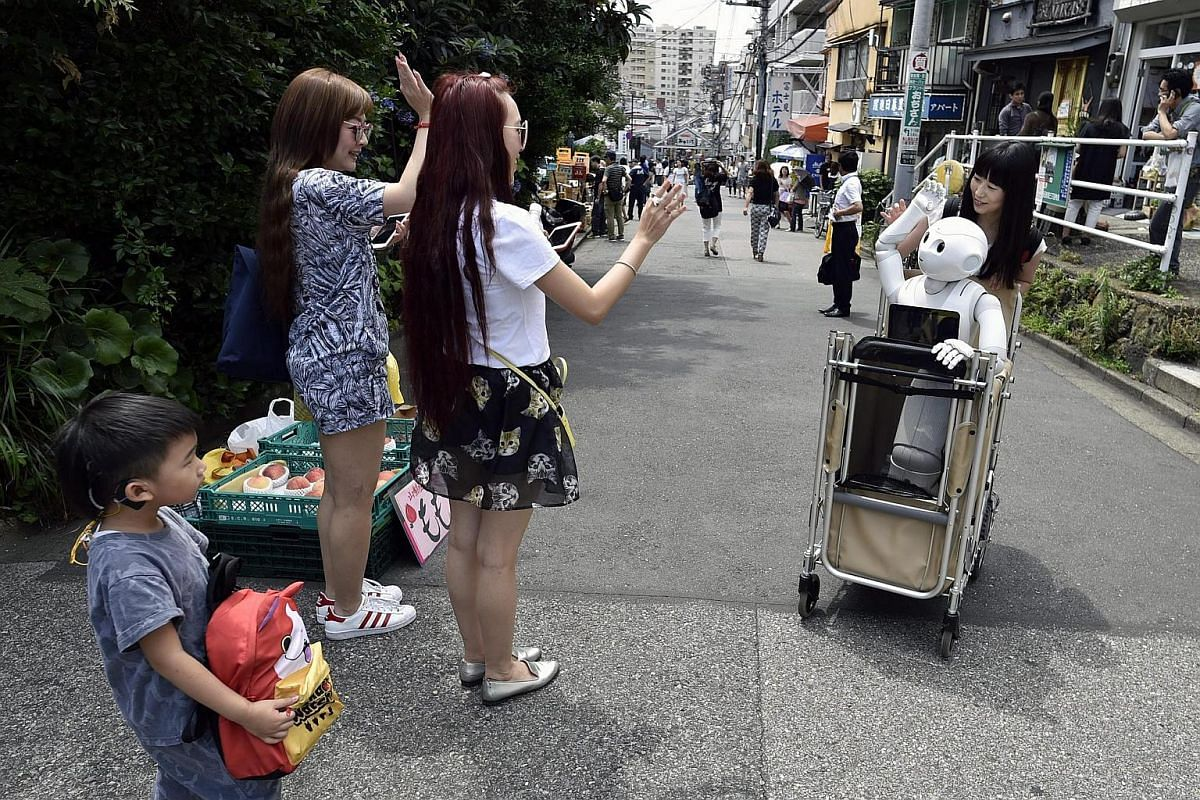 Tourists react as they see Tomomi Ota (right) pushing a cart loaded with her humanoid robot Pepper.
