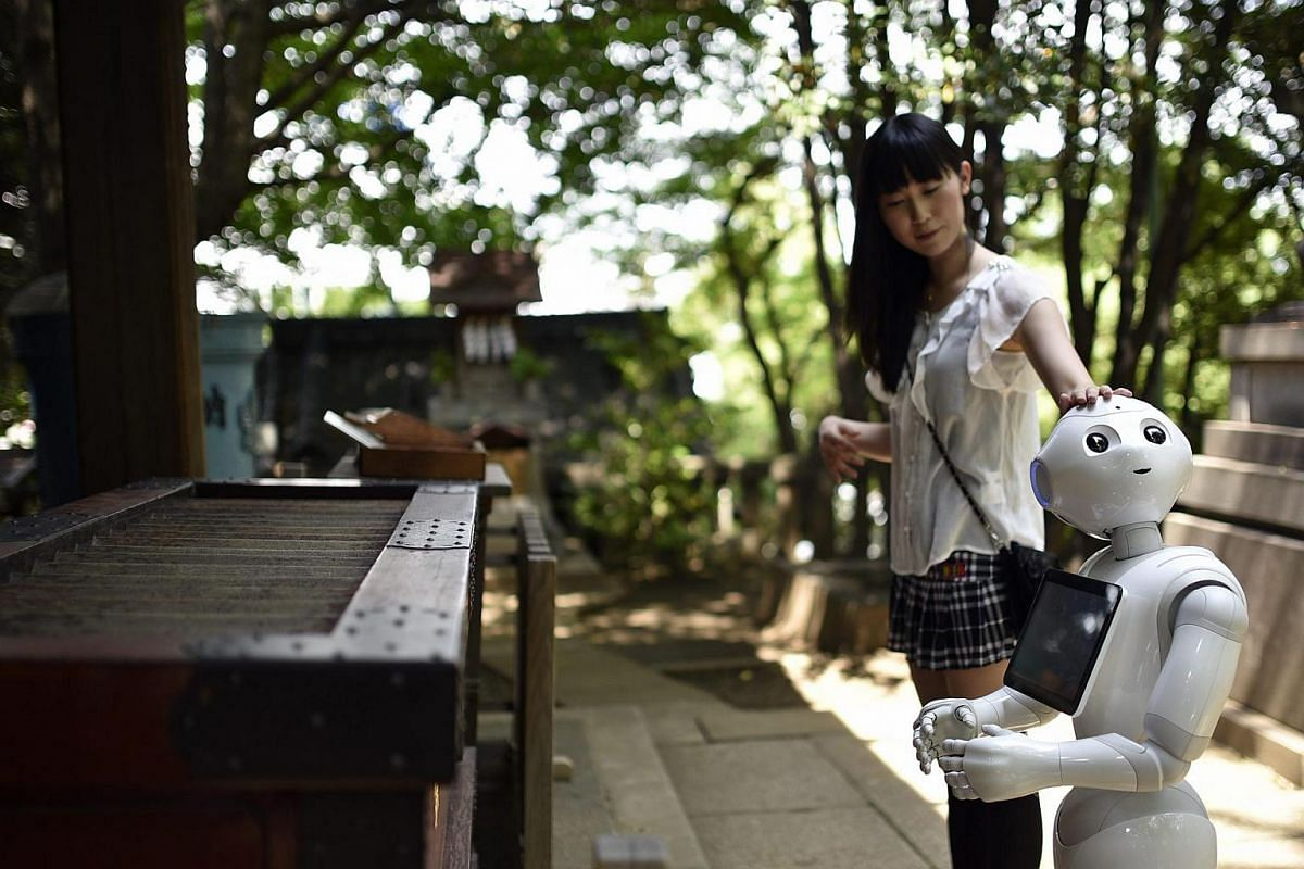 Tomomi Ota visits a local shrine with her humanoid robot Pepper.
