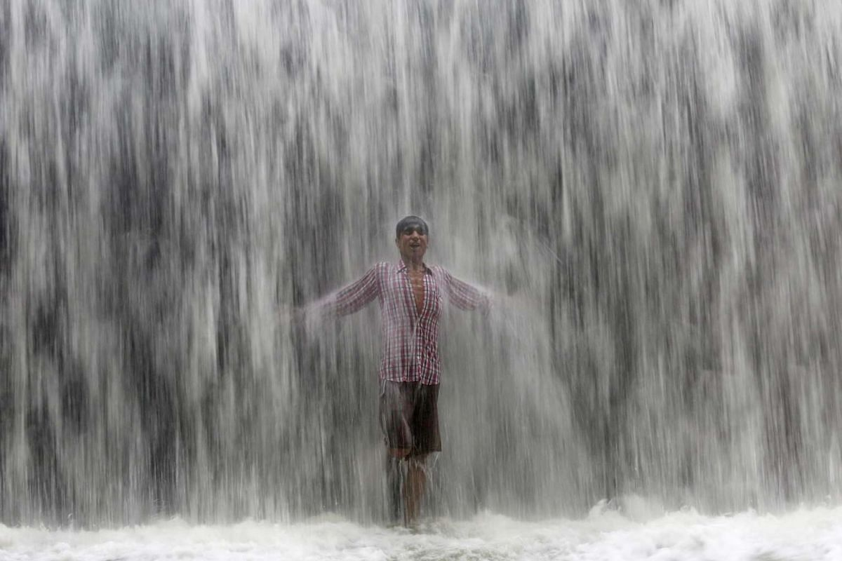 A boy stands under an overflowing dam along the Powai lake after heavy rains in Mumbai, India, on July 4, 2016.
