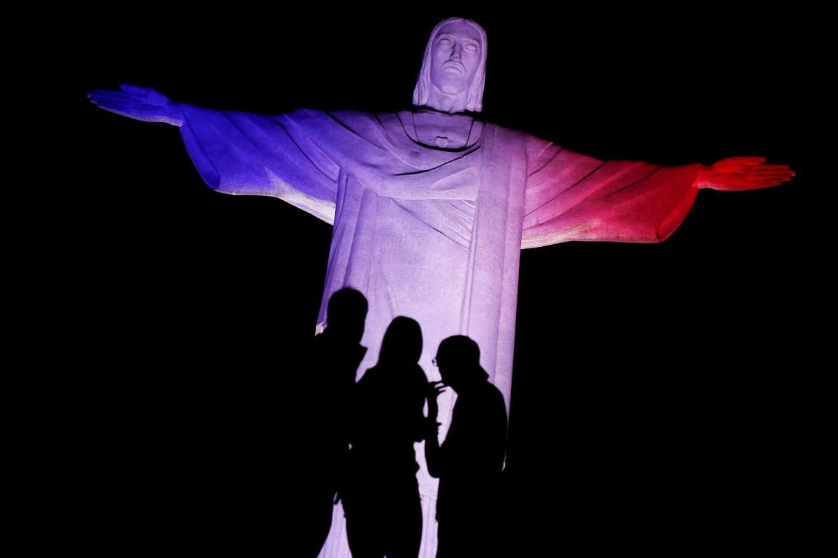 Tourists look on as the Christ the Redeemer statue is lit up in the colours of the US flag in celebration of its Independence Day in Rio de Janeiro, Brazil, on July 4, 2016.