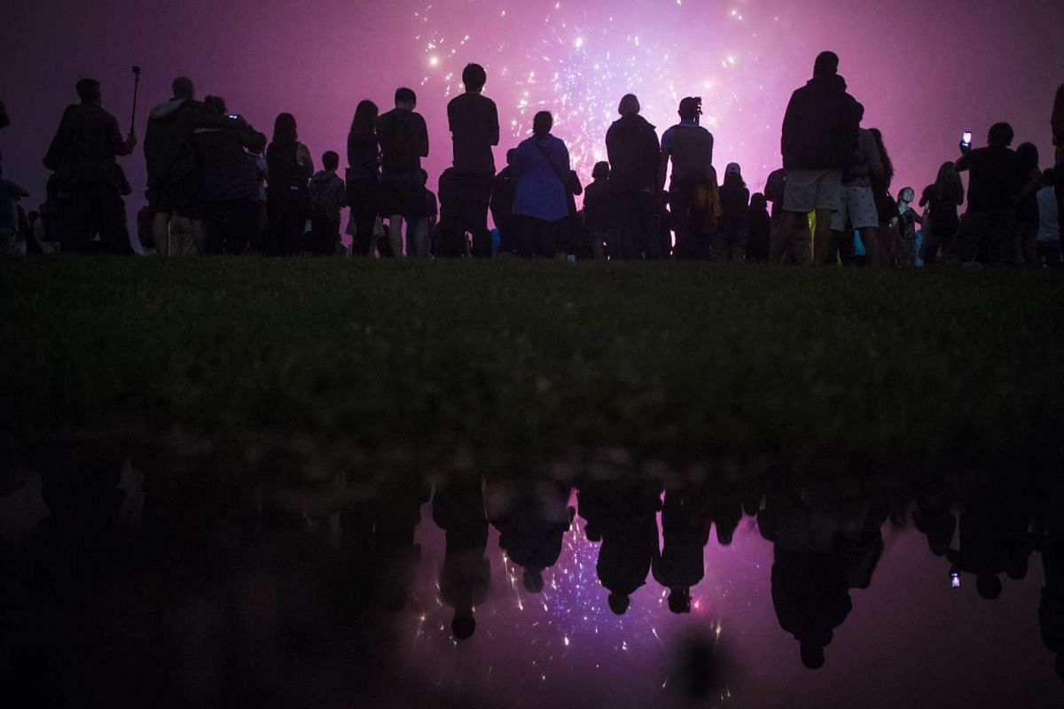 People, reflected in a rain puddle, stand in front of the Washington Monument as the Fourth of July fireworks go off on the National Mall on July 4, 2016.