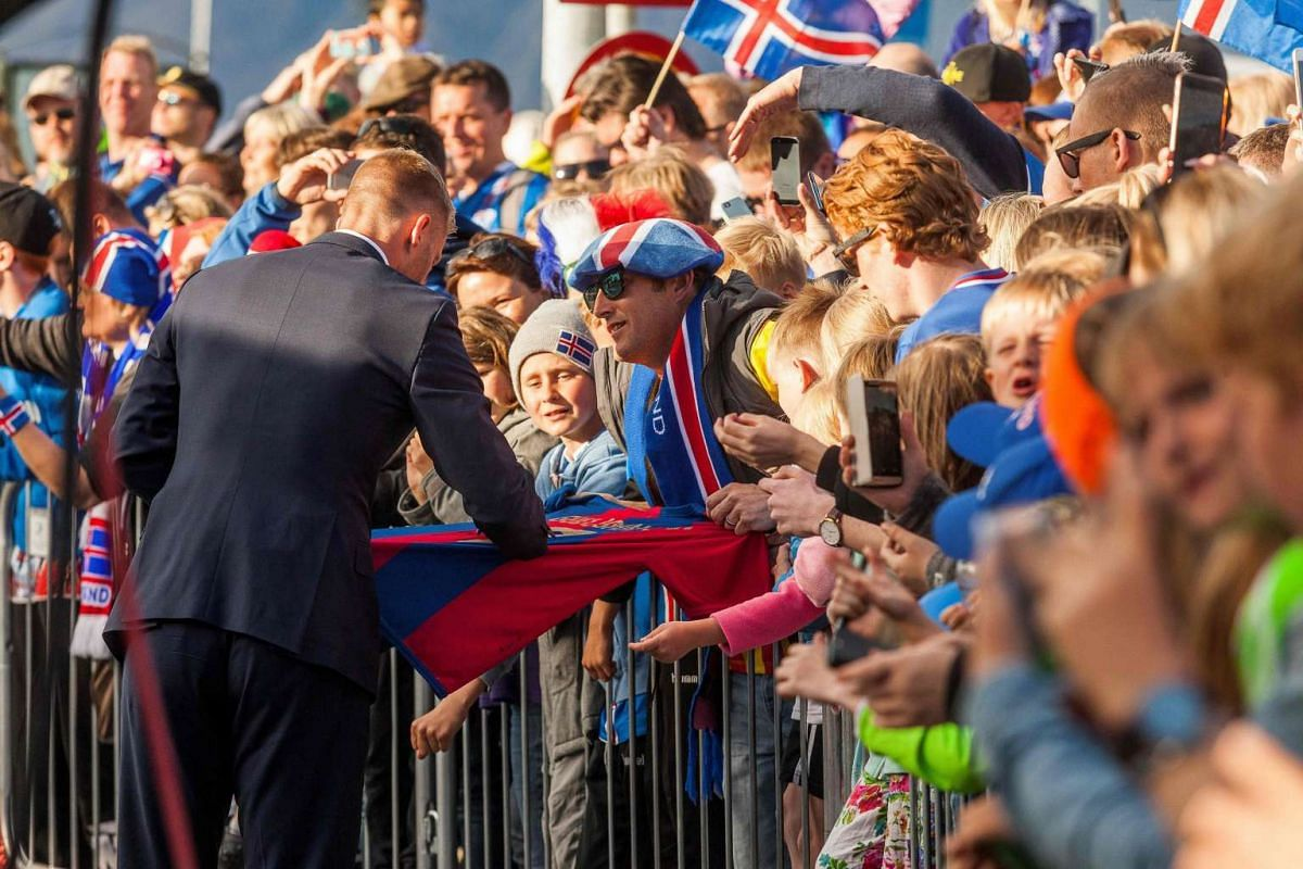 An Iceland national football player signs an autograph as he arrives with his team in Reykjavik.