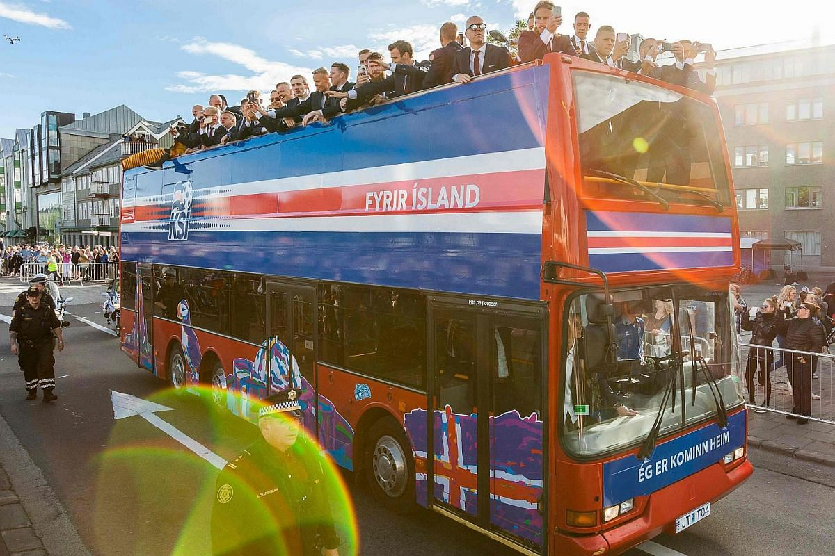 Iceland's national football team arrives in Reykjavik on July 4 on a bus while people in the streets greet them as winners despite their lost against France during the the Euro 2016 quarter-final football match.