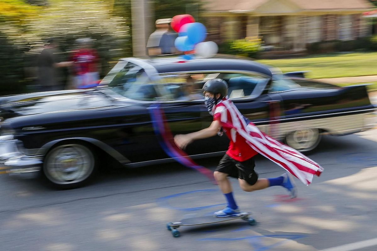 A boy rides a skateboard while participating in the Avondale Estates 4th of July Parade in Georgia.