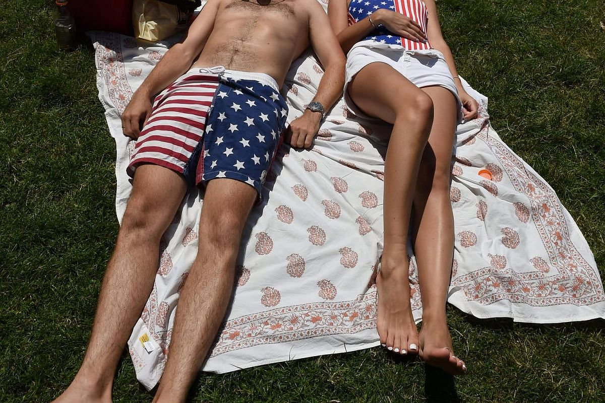 A couple relaxes in the Sheep Meadow in Central Park, wearing red, white and blue outfits as the US celebrates the Independence Day holiday in New York.