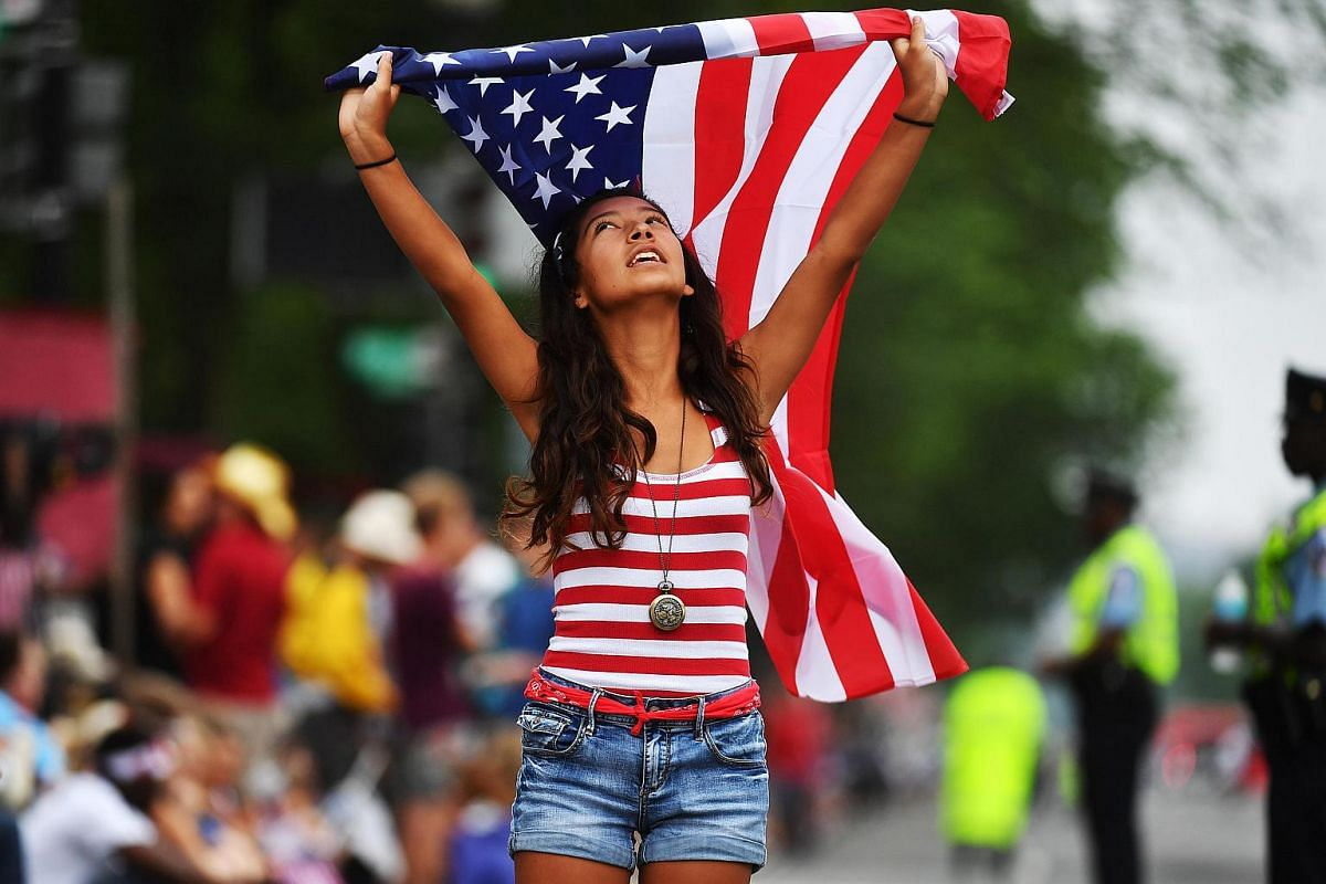 Jackie Pinos, 15, of Boynton Beach, Fla, joins in the festivities for Independence Day despite the cloudy and rainy weather in Washington, DC.