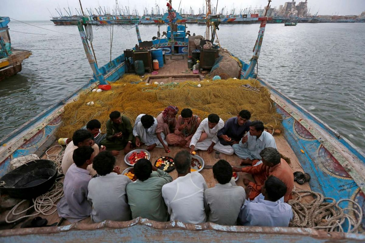 Haji Husain sits with colleagues to eat iftar on a fishing boat during the Muslim holy month of Ramadan in Ibrahim Hyderi, on the outskirts of Karachi, Pakistan on June 12, 2016.