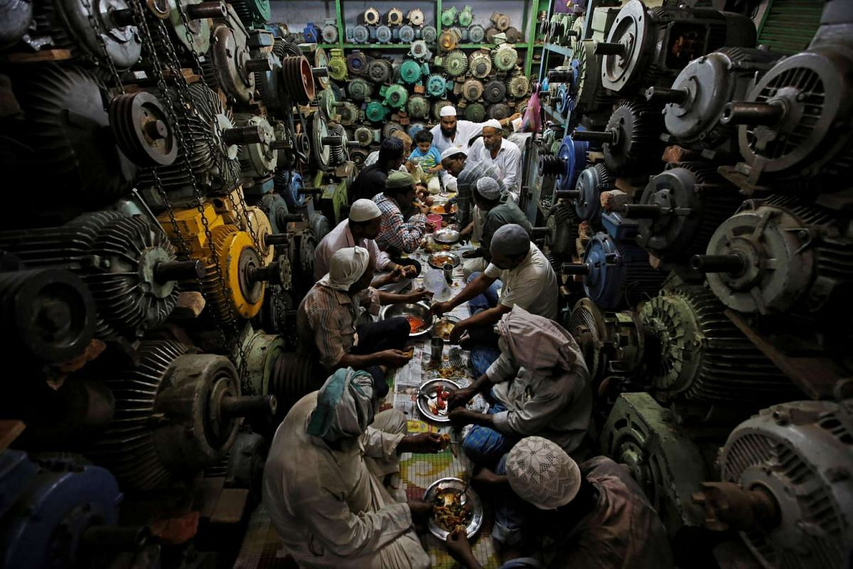 Anwaar Hussain, his coworkers and employer eat iftar inside a shop in the old quarters of Delhi, India, on June 14, 2016.