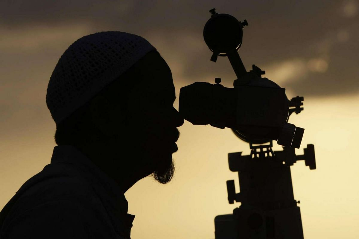 A Muslim man observes the position of the moon using a telescope to determine the end of the month of Ramadan as well as the first day to celebrate Eid al-Fitr festival at Lhok Nga, Aceh, Indonesia, on July 4, 2016.