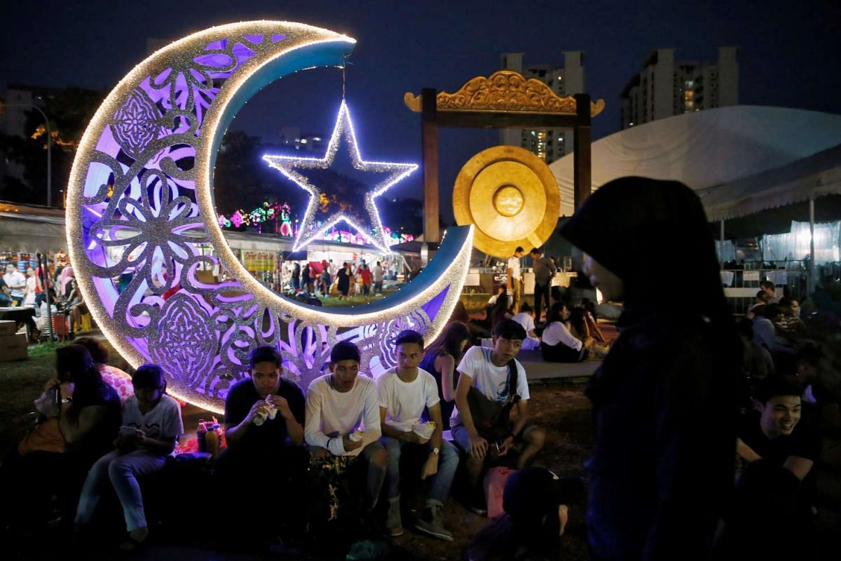 Youths break their fast at a bazaar ahead of Eid al-Fitr, which marks the end of the holy month of Ramadan, in Singapore, on July 4, 2016.