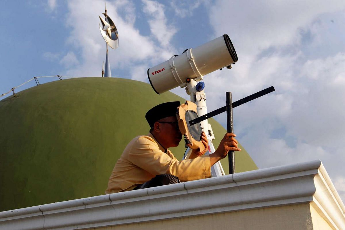A Muslim man uses a traditional tool to look at the position of the moon near the end of the holy fasting month of Ramadan at Al-Musyari'in mosque in Jakarta, Indonesia, on July 4, 2016.