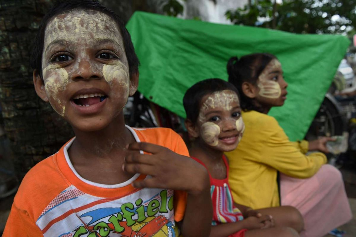 "Myanmar children wearing ""thanaka"", a traditional facial cosmetic, wait for alms outside a mosque in Yangon on July 6, 2016."