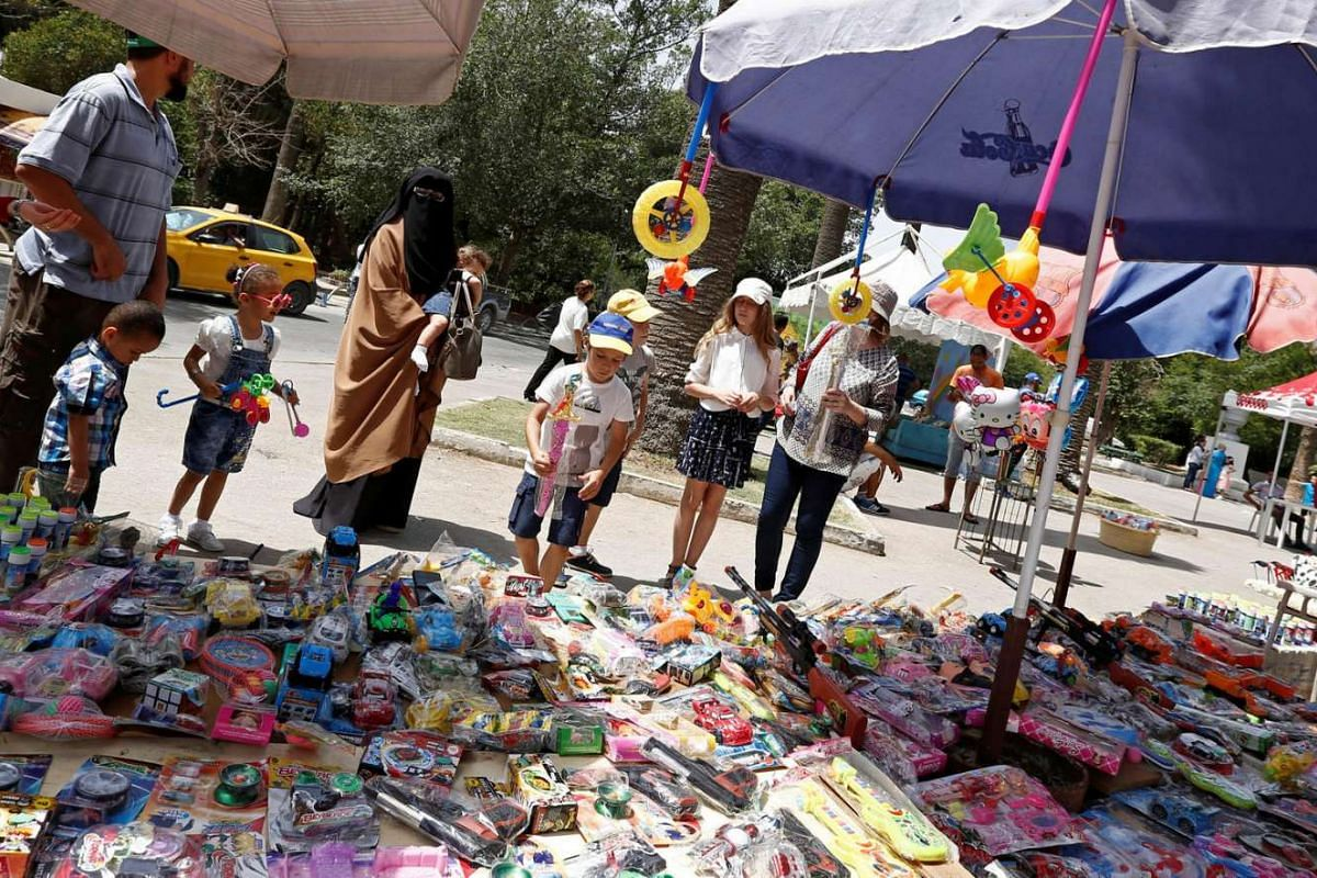 Children browse toys during the first day of the Muslim holiday of Eid al-Fitr in Tunis, Tunisia on July 6, 2016.