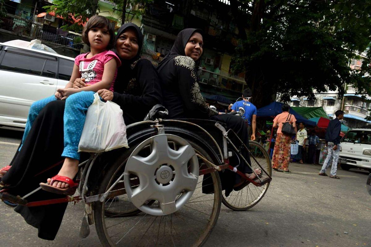 Myanmar Muslim women ride a trishaw outside a mosque in Yangon on July 6, 2016.
