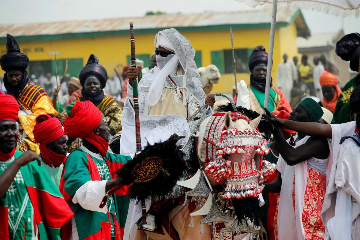 Emir of Kano, Muhammad Lamido Sanusi II (centre), rides a horse after attending the Eid al-Fitr prayers at Kofa Mata praying ground, to mark the end of holy month of Ramadan, in Nigeria's northern city of Kano, July 6, 2016.