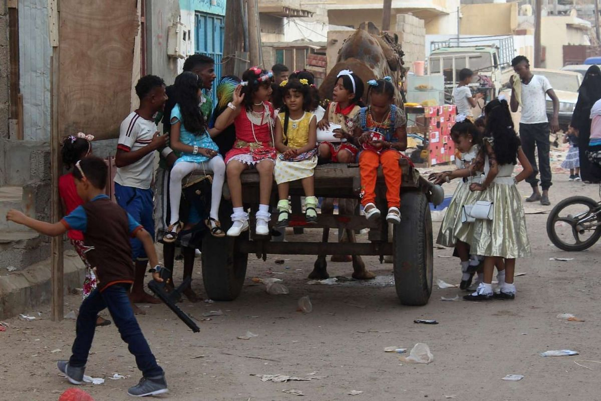 Yemeni girls sit on the back of a camel-drawn cart as people gather in the street during celebrations for Eid al-Fitr in Aden's northern Dar Saad district on July 6, 2016.
